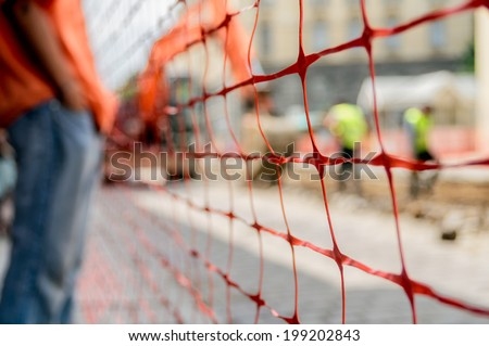 orange construction site net around construction site - stock photo