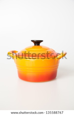Orange cooking pot with lid on a white background - stock photo