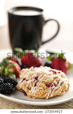 Orange Cranberry Scone with fresh fruit.  Shallow depth of field. - stock photo