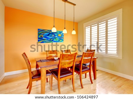 Orange dining room with wood table and hardwood floor. - stock photo