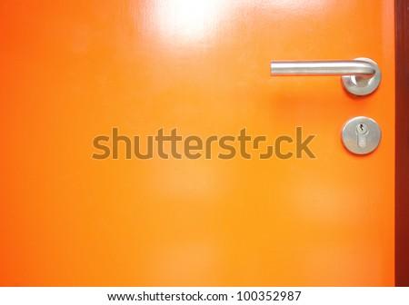 orange door with Metal door handle - stock photo