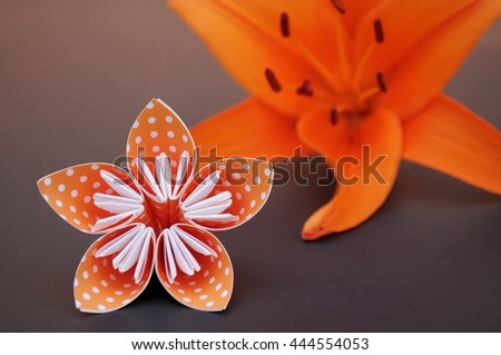 Orange (dotted) origami flower beside real orange lily blossom. Selective focus. - stock photo