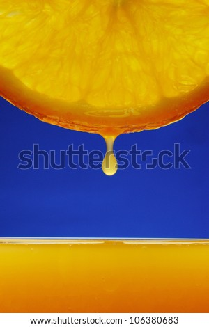Orange drop with blue background - stock photo