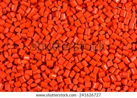 orange dyed plastic granulate for injection molding process - stock photo