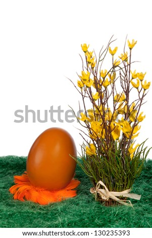 Orange Easter Egg on a bed of feathers with cheerful yellow spring flowers on green grass against a white background with copyspace for your Easter greeting - stock photo