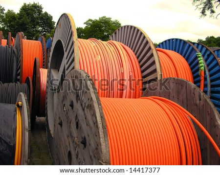 orange electricity cable on wooden spools - stock photo