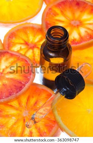 Orange essential oil in bottle with blood orange slices  - stock photo