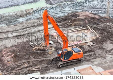 Orange excavator on a construction site - stock photo