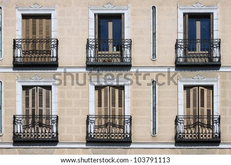 Orange facade Madrid residential building with balconies - stock photo