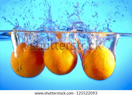 Orange falls into the water and making splashes - stock photo