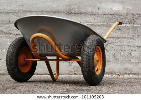 orange farmer's two wheelbarrow on concrete background - stock photo