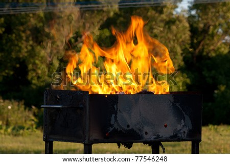 Orange flames leaping over an open empty grill outdoors - stock photo
