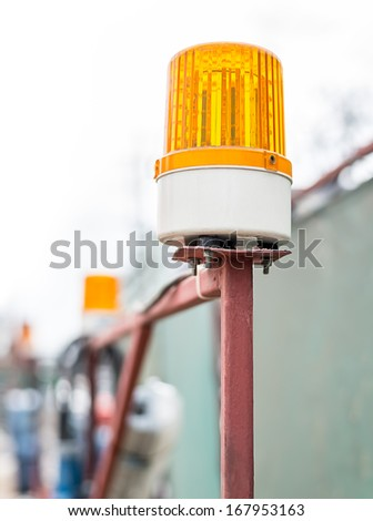 Orange flashing beacon in the place of work - stock photo