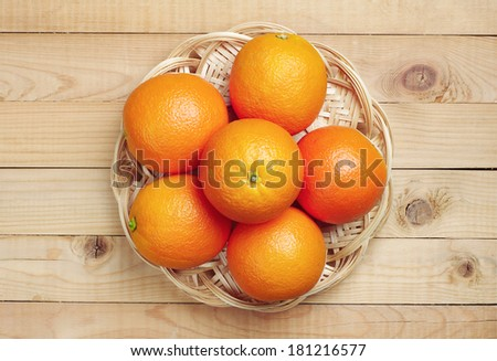 Orange fruit in wicker plate on wooden background. Top view - stock photo