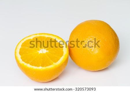 Orange fruit with half sliced on white background - stock photo