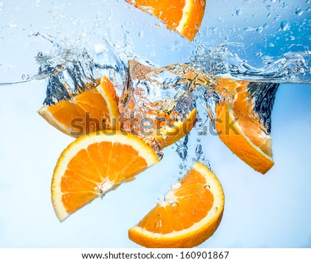 Orange fruits fall deeply under water with a big splash - stock photo