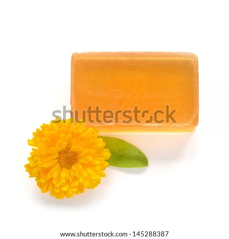 Orange handmade glycerin soap and marigold flower on white background. Hypoallergenic soap with marigold extract. Beauty care. - stock photo