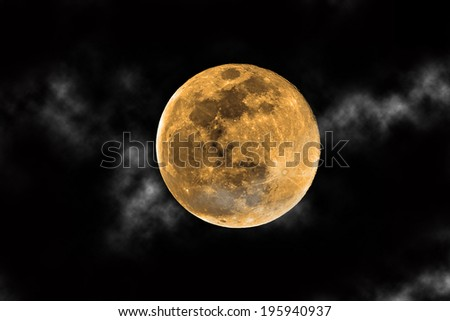 orange harvest moon and clouds against black sky - stock photo