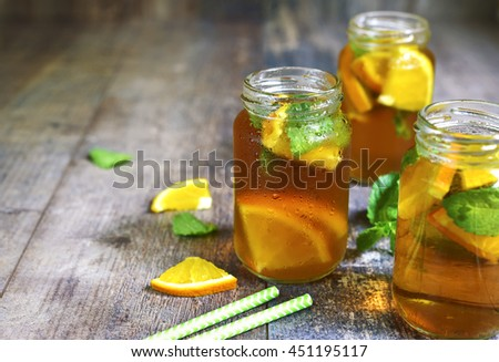 Orange iced tea in a glass jar on a rustic wooden background. - stock photo