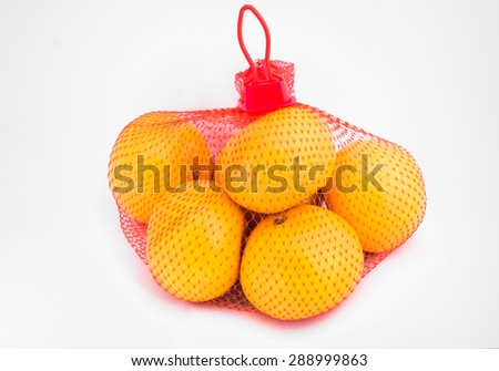 orange in red net bag on white background - stock photo
