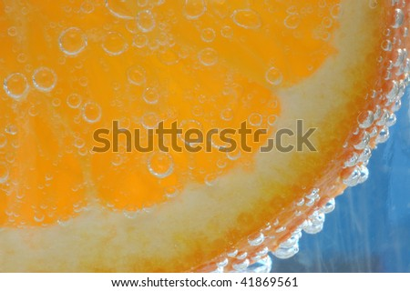 Orange in soda water with blue background - stock photo