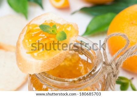 orange jam in a glass jar and piece of baguette, close-up - stock photo