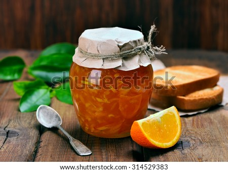 Orange jam in glass jar and slices on wooden table - stock photo