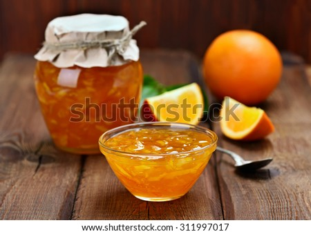 Orange jam on wooden table - stock photo