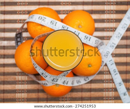 Orange juice and fresh oranges around glass wrapped with measuring tape - stock photo