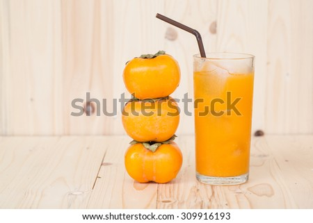 Orange juice and persimmon on wooden background - stock photo