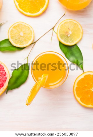 orange juice glass with  slices of citrus and green leaves on white wooden background, top view - stock photo