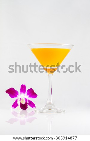 Orange juice in a cocktail glass on white background with orchid flower - stock photo