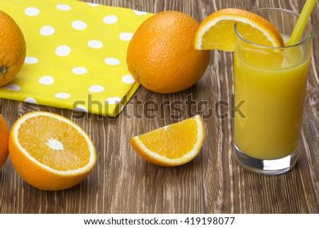 Orange juice in glass,  fresh fruits on wooden background - stock photo
