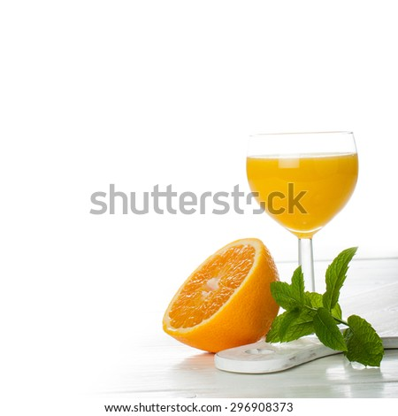 Orange juice in glass with slice of orange and fresh mint on white background. Healthy food concept with copy space for text. - stock photo