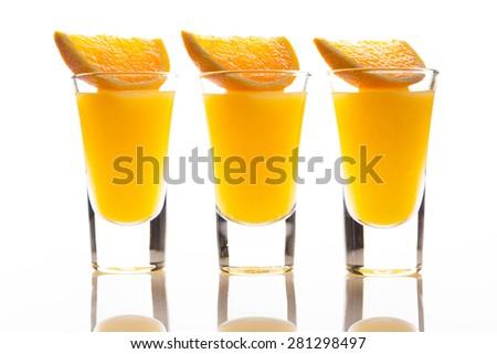 Orange juice in shot glass. Isolated on white background. - stock photo