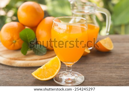 Orange juice is placed on a wooden table with natural light. - stock photo