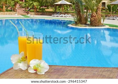 Orange juice on the swimming pool                                - stock photo
