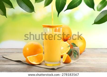 Orange juice on wooden table on nature background - stock photo