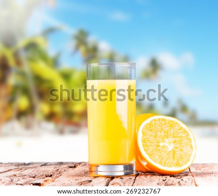 Orange juice on wooden with tropical beach , fresh summer drink, summer concept - stock photo