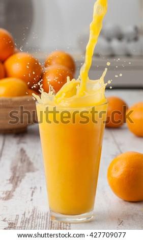 Orange juice poured in a glass with splash. - stock photo