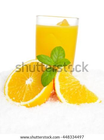 Orange juice with ice cubes and orange fruit with citrus leaves on ice on white background - stock photo