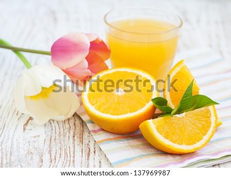 Orange juice with sliced orange and tulips on the wooden background - stock photo