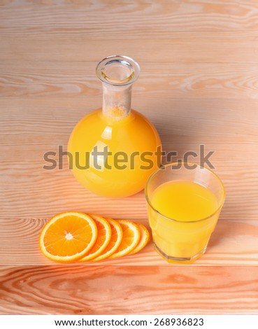 Orange juise in bottle and glass with orange slices - stock photo