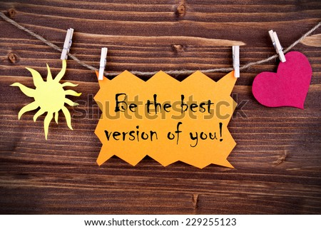 Orange Lable Saying Be The Best Version Of You On Wooden Background Hanging On A Line, One Red Heart Symbol And One Yellow Sun Symbol Background Is Old Fashion - stock photo