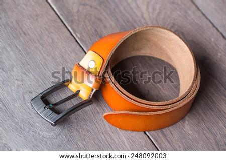 Orange leather belt on wood background - stock photo