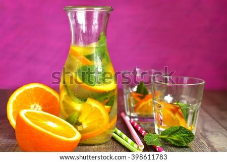 Orange lemonade in a bottle on a pink background. - stock photo