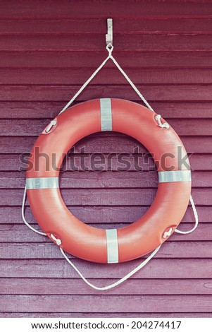 Orange life-buoy hanging on red wooden wall - stock photo