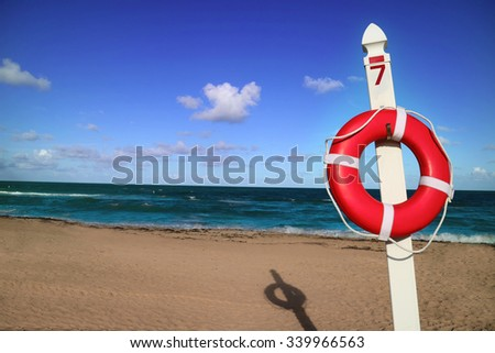 Orange lifebuoy ring, life preserver on a pole number 7. Blue sky, some clouds, sea and sun in background. Miami, Florida.     - stock photo