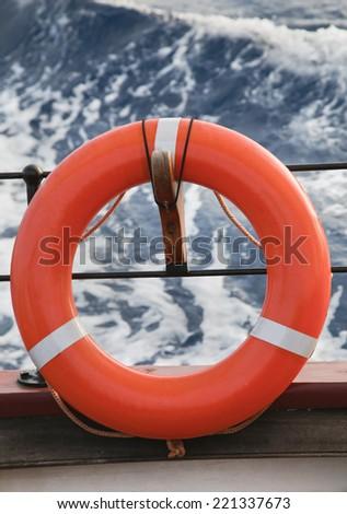 Orange lifesaver hanging on a bord of a sailing ship - stock photo