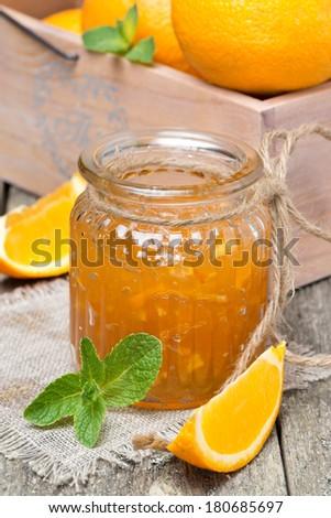 orange marmalade in a glass jar, vertical, close-up - stock photo